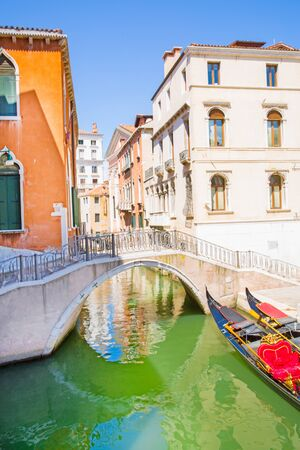 Narrow canal and gondola in Venice, Italy. Old colorful building facades and green water. 写真素材
