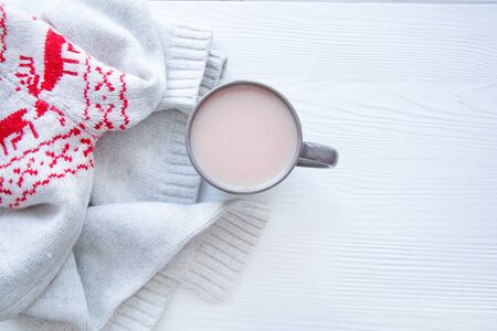A cup of tasty cacao and woolen winterornament sweater on white wooden table background