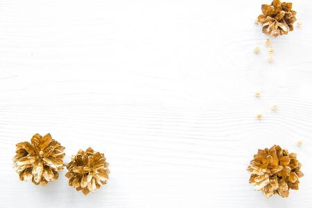 Christmas golden cones and beads on white bright background