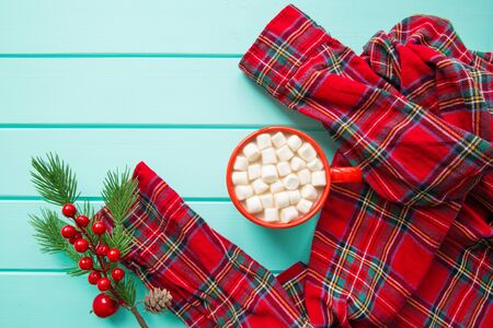 Christmas cocoa with marshmallow on wooden turquoise table and red tartan shirt. Top view. Christmas decorations.