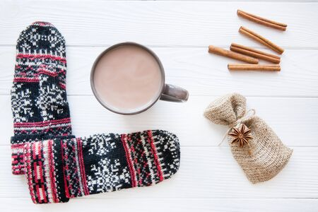 A cup of hot cocoa with cinnamon and Christmas ornament gloves on white wooden background.