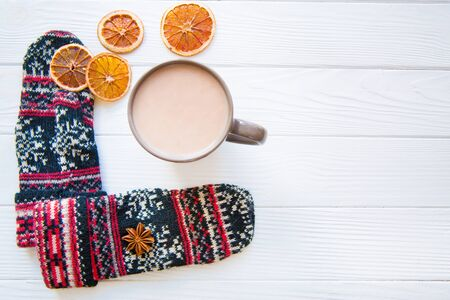 A cup of hot cocoa, dried oranges and Christmas ornament on white wooden background. 写真素材