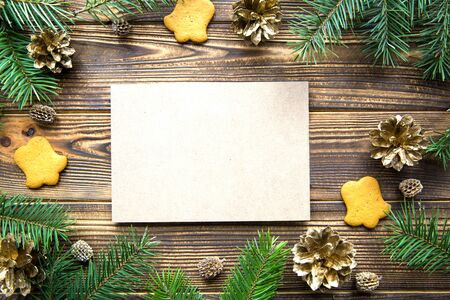 Christmas background, golden cones, gingerbread cookies and fir tree branches and empty card for text invitation, rustic table.