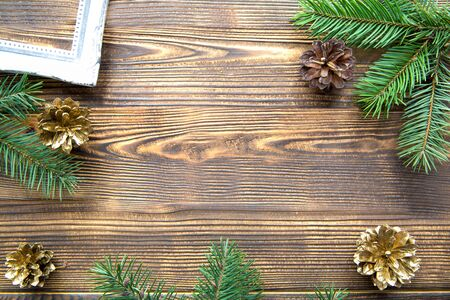 Christmas rustic background. Pine cones, fir tree branches and frame on brown table.
