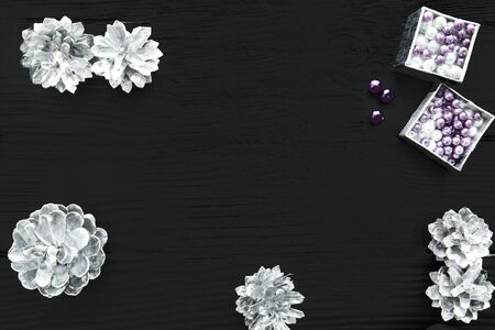 Silver Christmas decorations background with free copy space for text and greeting. PInecones and beads, top view.