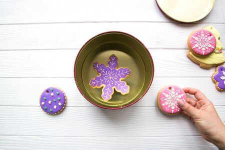 Hand hold Christmas gingerbread cookie and put it in the box. Assortment of  cookies, top view. 写真素材