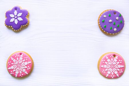 Icing gingerbread cookies on white wooden table, copy-space, space for text. Traditional Christmas homemade baking.