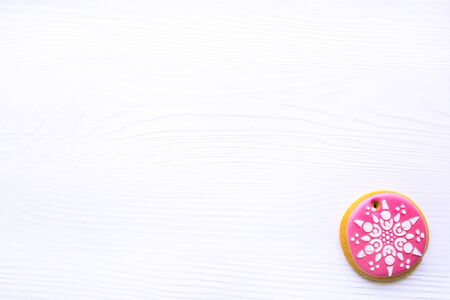 Icing gingerbread pink cookie on white table. Traditional Christmas homemade baking. 写真素材
