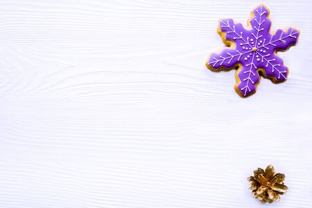 Snowflake gingerbread cookie on white Christmas table background, top view.