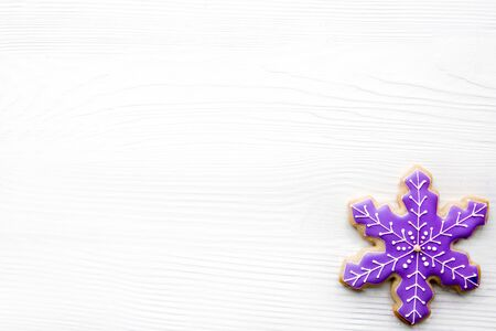 Icing snowflake gingerbread cookie on white background, top view. Traditional Christmas baking.
