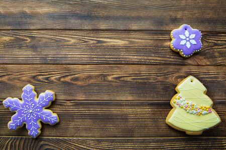 Homemade traditional gingerbread cookies on brown wooden background