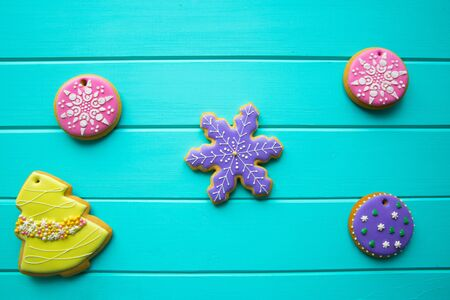 Assorment of traditional gingerbread cookies for Christmas on turquoise background, top view. Christmas tree, snowflakes and balls.