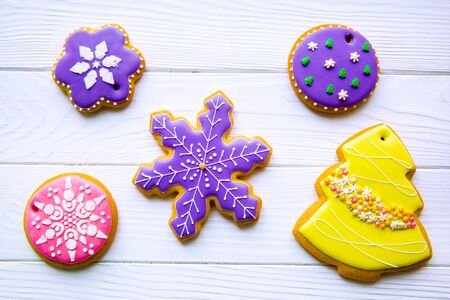 Assorment of traditional frosted gingerbread cookies for Christmas on white background, top view. Christmas tree, snowflakes and balls.