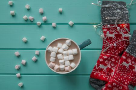 A cup of hot chocolate drink with marshmallow and red woollen socks with winter ornament on wooden table, top view. Festive Christmas lights.