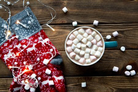 A cup of hot chocolate drink with marshmallow and red woollen socks with winter ornament on wooden table, top view. Festive Christmas lights. 写真素材