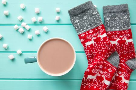 A cup of tasty cocoa drink on bright turquoise table, top view. Christmas socks with deer ornament.  写真素材