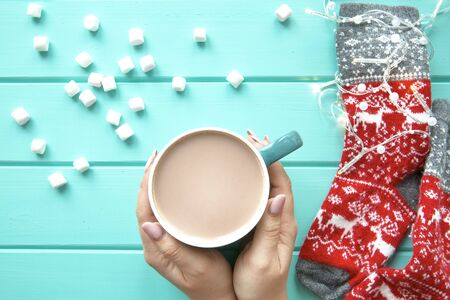Hands holding a cup of tasty cocoa with marshmallow, festive lights and red woolen socks on wooden background, top view.