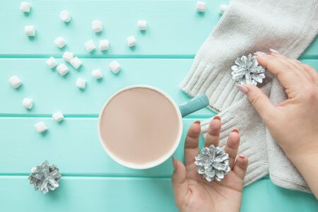 A cup of winter beverage with sweets and Christmas silver cones, turquoise table background, top view.