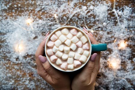Hand holding tasty hot cocoa with marshmallow on snowy background and lights, top view.