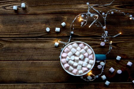 Tasty hot chocolate with marshmallow on brown wooden rustic table, yellow Christmas lights. Space for text, copy space.