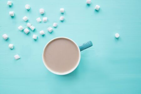 A cup of delicious cocoa with marshmallow on turquoise background, space for text, copy space.