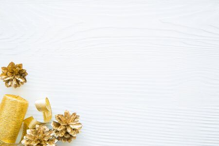 Festive Christmas background with space for text. Golden pinecones and candle decorations on white background.