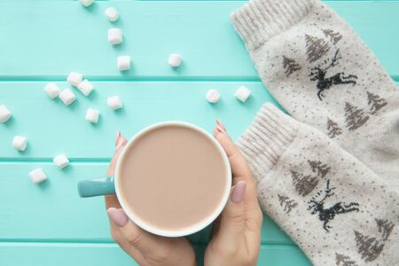 A cup of tasty cocoa with marshmallow, top view. Winter deer ornament traditional socks.