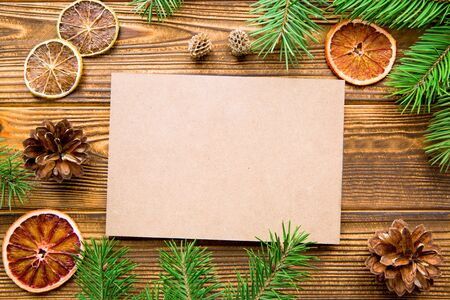 Empty card on wooden table background. Holiday winter decorations. Space for greeting and invitation.
