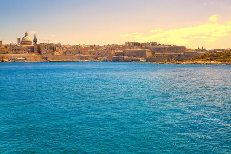 Malta, Sliema. Panoramic view of Mediterannean sea and old town buildings, colorful bright sky.  写真素材