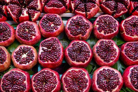 Many pomegranate cut in half, bright colors. Tasty juicy fruit on market.