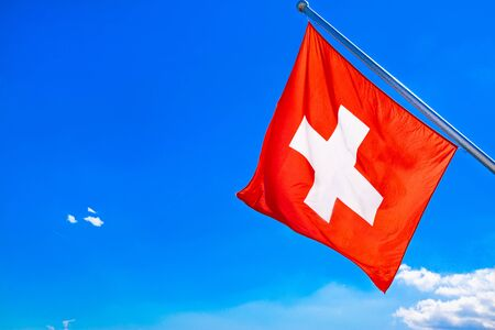 Switzerland flag waving in the wind, blue sky and clouds. Bright red color, sunny weather.