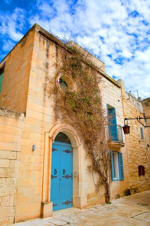 Malta blue door and bright summer sky,  typical Maltese street architecture.