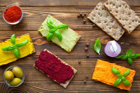 Tasty hummus snack, assorment of paprika, avocado, beetroot and curry hummus on rustic brown table background.