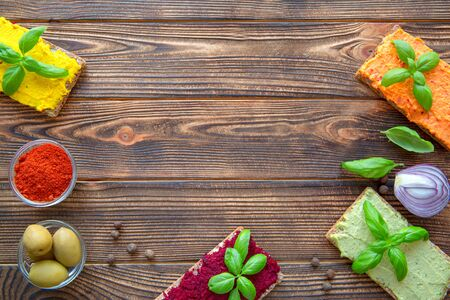 Assortment of hummus starters, tasty arabic and israeli snack on wooden rustic table, top view. Copy space, space for text, top view.