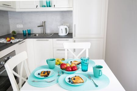 Healthy breakfast in modern design kitchen in white, grey and turquoise colors. Toasts with fruits.  Reklamní fotografie