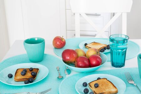 Stylish turquoise plates and cups in modern kitchen. A lot of turquoise accessories. Tasty breakfast, bright colors.