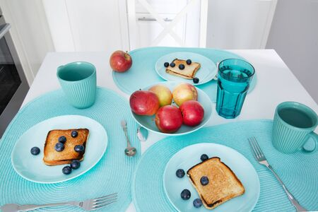 Served breakfast table, fresh fruits and grilled toasts. Plates and dishes.