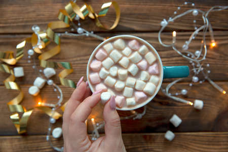 A cup of hot chocolate beverage, female hands and lights, top view. Christmas holiday mood. Zdjęcie Seryjne