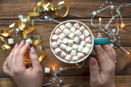 A cup of hot cocoa beverage, female hands and lights, top view. Christmas holiday mood.