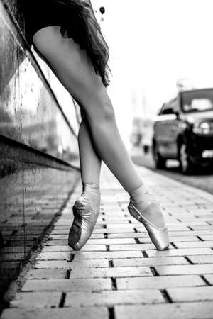 The beautiful legs of a ballerina in pointe shoes are shot on the street. Stock Photo