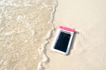 Waterproof case on a smartphone, phone for taking pictures under water. Phone in the waterproof case underwater, on the sands.