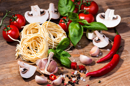 Pasta ingredients on a wood background photo