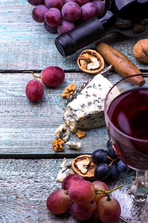 uvas: botella de vino tinto, las uvas, las nueces y el queso en un fondo de madera