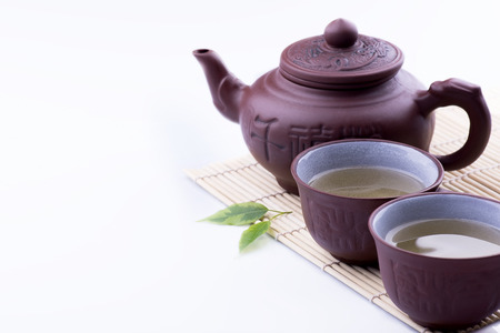 tea set: Green Tea set on a bamboo mat on white background Stock Photo