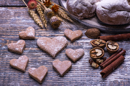 kiss biscuits: Baking ingredients for making biscuits, cookies in the shape of heart on wooden board. St.Valentine s Day Stock Photo