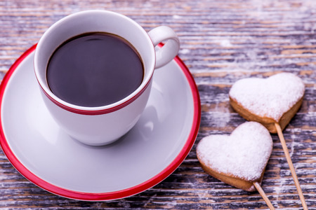kiss biscuits: Coffee cup and biscuits, cookies in the shape of heart on wooden background. St.Valentines Day. Stock Photo