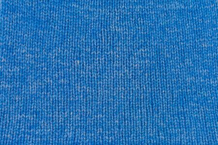 Needlework, hobbies, knitting. Background textile fabric with a knitted texture wool blue. Blue knitted fabric texture. Hand knitting.