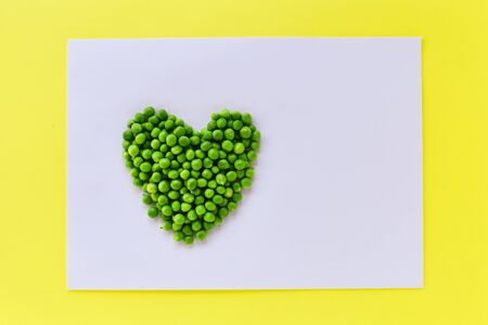 Heart made of green peas on a white background in a yellow frame. The concept of proper nutrition.