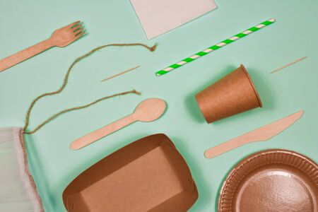 Zero waste, environmentally friendly, disposable, cardboard, paper utensils on a blue background. View from the top.