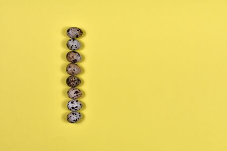 A row of Easter eggs on a yellow background. Easter concept. View from above. Place for an inscription. The basis for the postcard. Vertical row.